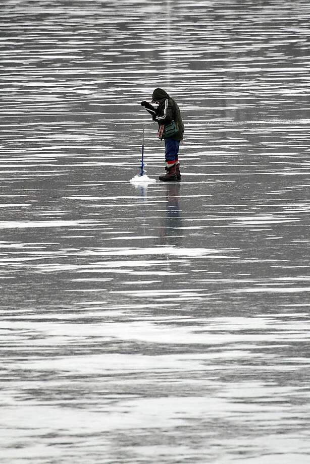 An ice fisherman uses a hand auger to drill through ice to set a tip up at Lackawanna State Park in North Abington Township Wednesday, Jan. 9, 2013. Photo: Michael J. Mullen, Associated Press