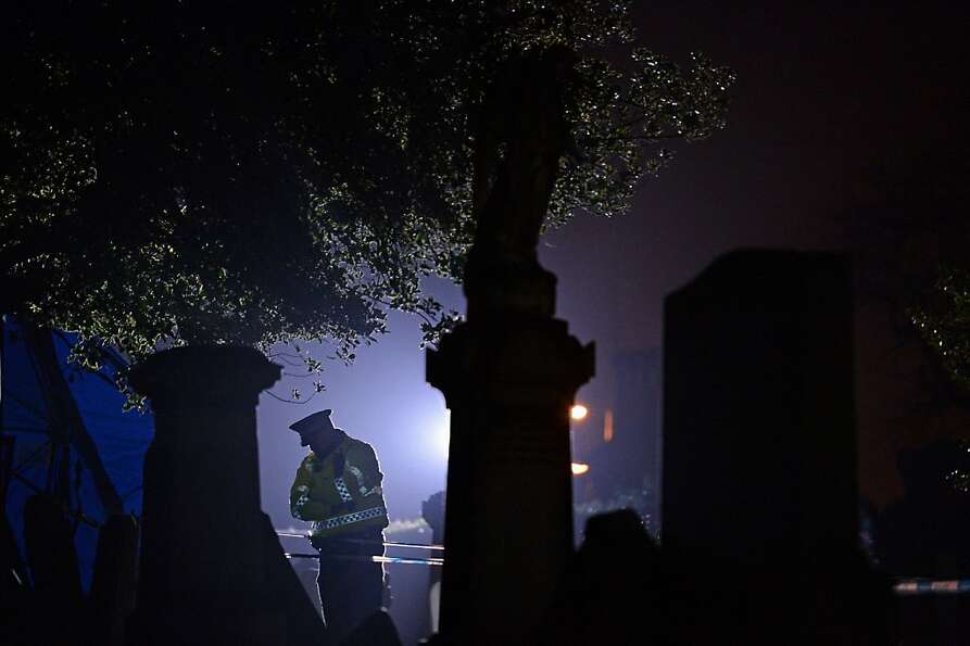 A police officer stands on duty at Monkland Cemetery as forensic officers continue to exame a burial