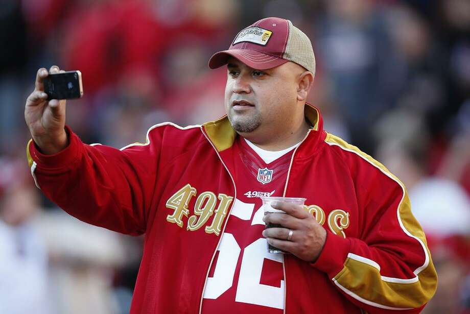 Dec. 30, 2012: A 49ers fan checks out his iPhone during a game against the Arizona Cardinals at Candlestick Park. This looks like a possible self-portrait, but for the sake of now/then continuity, let's assume it's a television replay. Photo: Stephen Lam, Special To The Chronicle / ONLINE_YES