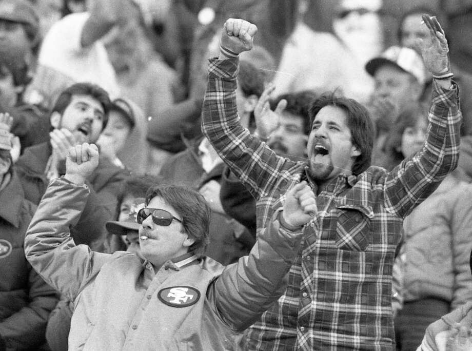 Dec. 22, 1985: Two San Francisco 49ers fans celebrate a touchdown -- and prove that the smoking rules were much more relaxed in 1985 during a game against the Dallas Cowboys. Photo: Tom Levy, The Chronicle / ONLINE_YES