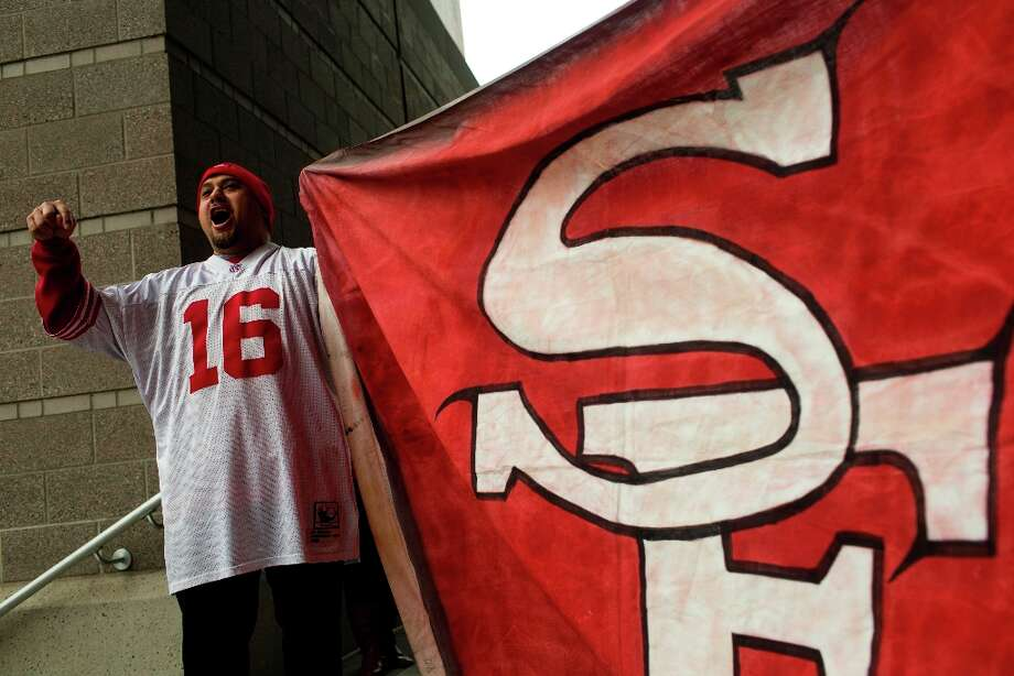 Dec. 23, 2012: Washington resident and 49ers fan Jessie Leota cheers while showing off his custom-made flag outside of the stadium in the hours before the Seahawks/49ers game at CenturyLink Field in Seattle. (Jordan Stead / Special to the Chronicle) Photo: JORDAN STEAD, SFC / ONLINE_YES