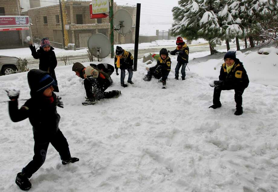Syrian refugee children have a snowball fight at the mountain town of Bhamdoun, east of Beirut, Lebanon, Wednesday, Jan. 9, 2013. The fiercest winter storm to hit the Middle East in years has unleashed flash flooding, strong winds and a snowstorm that killed six people in the past few days, according to the Lebanese Red Cross. The Lebanese mountains have been covered with record snow fall that has brought traffic to a standstill and shut down mountain passes across the country. (AP Photo/Bilal Hussein) Photo: Bilal Hussein