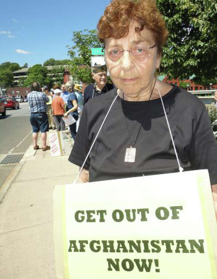 Estelle Margolis, at a weekly peace vigils she organizes at the Post Road bridge last June, was charged with breach of peace Tuesday after bringing a BB rifle and ammunition to a Representative Town Meeting on gun control. Photo: File Photo / Westport News
