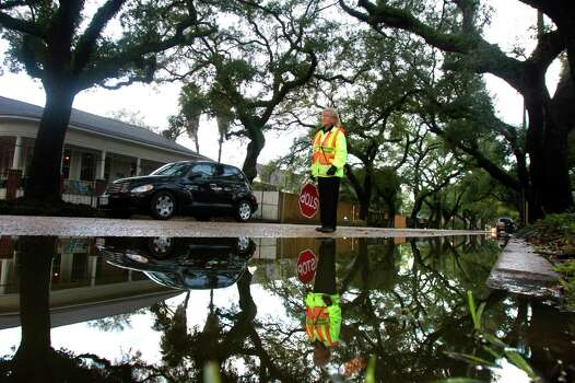 School Crossing Guard Dorothy Dames is reflected in a puddle as she stands along Bayland Street near Houston Avenue, Thursday, Jan. 10, 2013, in Houston. James said that the standing water usually stays about a week after the rain. Photo: Cody Duty, Houston Chronicle / © 2012 Houston Chronicle