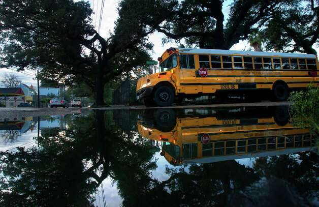 A school bus is seen reflected in standing water left from the rain, Thursday, Jan. 10, 2013, in Houston. Photo: Cody Duty, Houston Chronicle / © 2012 Houston Chronicle