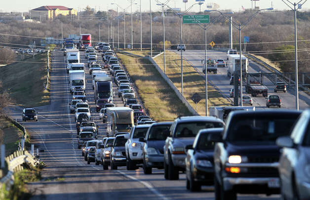 Traffic backs up on Interstate 10 westbound on San Antonio's East Side after more than a dozen  vehicles ran over a large pothole near the New Braunfels avenue bridge Thursday morning January 10, 2013. Traffic has been blocked in the center and right lanes to make it safer for motorists to change their tires and get back on the road. It is believed the pothole developed over time because of the recent rainfall. There were no injuries. Photo: JOHN DAVENPORT, San Antonio Express-News / ©San Antonio Express-News/Photo Can Be Sold to the Public