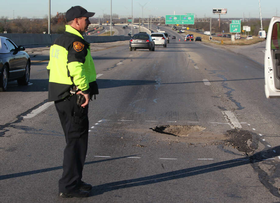 Traffic passes by a pothole on Interstate 10 westbound on San Antonio's East Side after more than a dozen  vehicles ran over it near the New Braunfels avenue bridge Thursday morning January 10, 2013. Traffic has been blocked in the center and right lanes to make it safer for motorists to change their tires and get back on the road. It is believed the pothole developed over time because of the recent rainfall. There were no injuries. Photo: JOHN DAVENPORT, San Antonio Express-News / ©San Antonio Express-News/Photo Can Be Sold to the Public