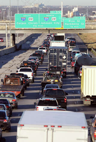 Traffic backs up on Interstate 10 westbound on San Antonio's East Side after more than a dozen  vehicles ran over a large pothole near the New Braunfels avenue bridge Thursday morning January 10, 2013. Traffic has been blocked in the center and right lanes (farther up from what this shows) to make it safer for motorists to change their tires and get back on the road. It is believed the pothole developed over time because of the recent rainfall. There were no injuries. Photo: JOHN DAVENPORT, San Antonio Express-News / © San Antonio Express-News