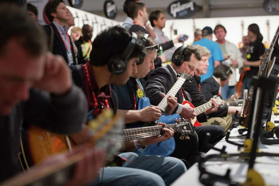 Attendees play Gibson Corp. guitars inside the Gibson tent. Photo: David Paul Morris, Bloomberg / © 2013 Bloomberg Finance LP