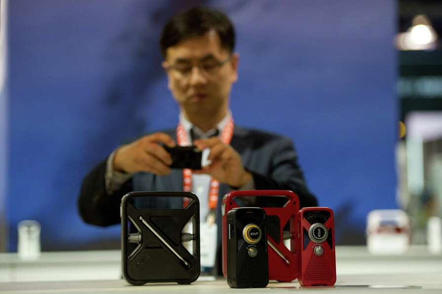 An attendee takes a photograph of Eton Corp. multi-purpose weather radio with smartphone chargers.