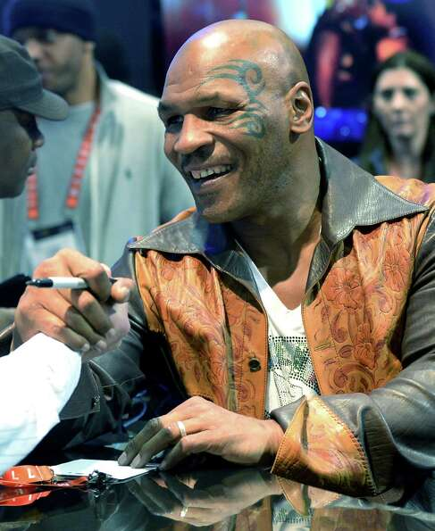 Retired US heavweight boxing  Mike Tyson signs autographs at SMS Audio booth at the 2013 Internation