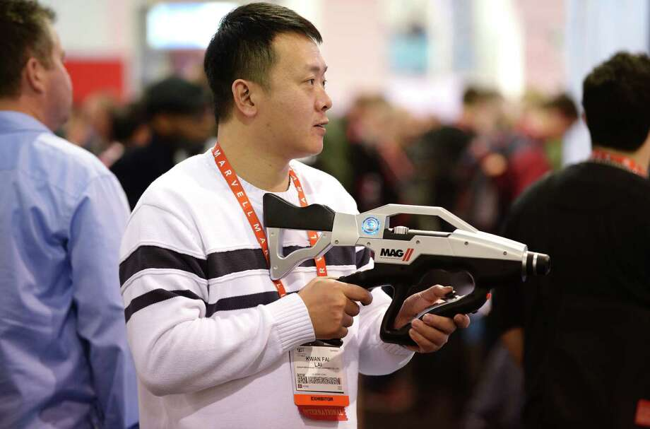 A man checks out video game gun MAG 2 by G-Mate at the 2013 International CES. Photo: JOE KLAMAR, AFP/Getty Images / AFP