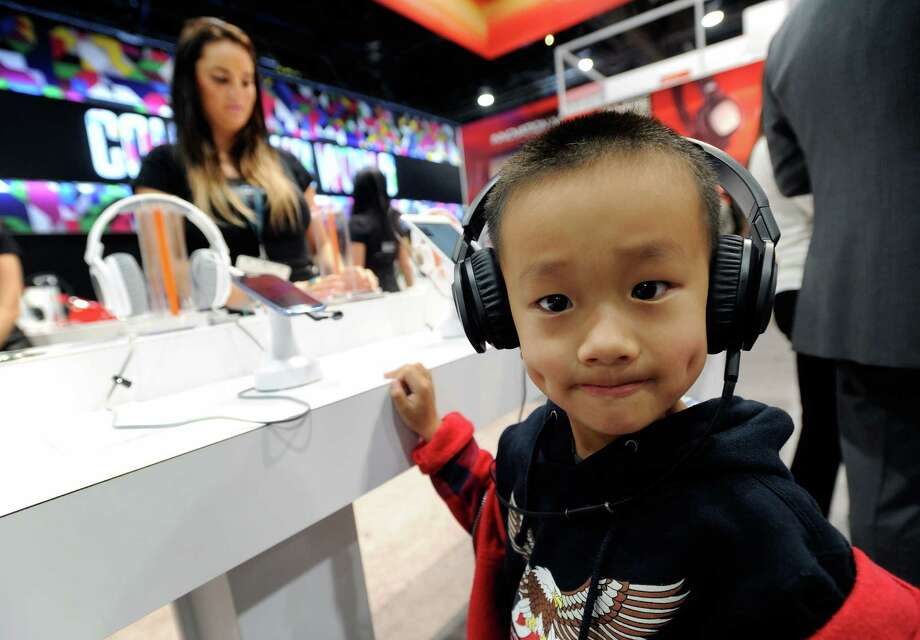 A young attendee listens to music on a pair of JBL J88i headphones at the Harman-Kardon booth Wednesday. Photo: David Becker, Getty Images / 2013 Getty Images