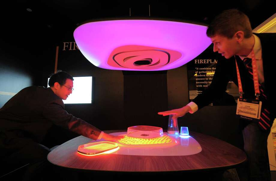 Whirlpool shows how their concept of a dining unit, called Fireplace, keeps food and atmosphere warm. Fireplace can keep foods warm and drinks cool. It adapts to the containers you put on it. Photo: JOE KLAMAR, AFP/Getty Images / AFP