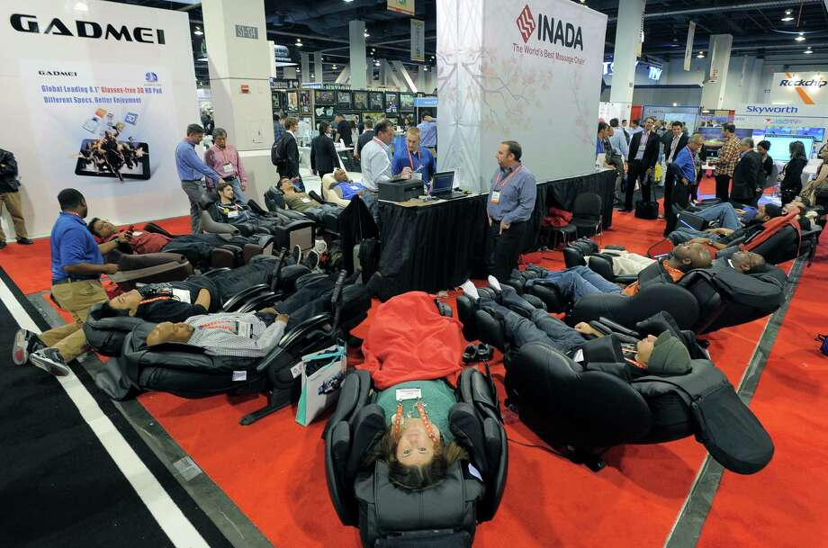 Consumers relax in massage chairs at Inada booth. Photo: JOE KLAMAR, AFP/Getty Images / AFP
