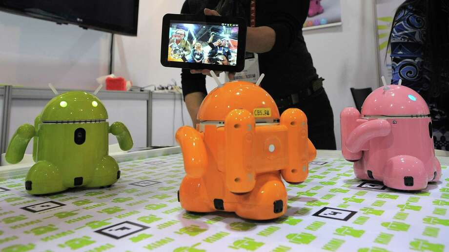 Mike Kim from Korea's Roboware operates smart device controlled toy robots. Photo: JOE KLAMAR, AFP/Getty Images / AFP