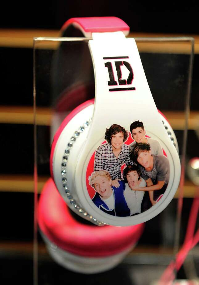 An image of the band, One Direction, covers a pair of headphones at the Jazwares booth Wednesday. Photo: David Becker, Getty Images / 2013 Getty Images