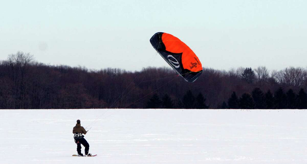 Snowkiting It's similar to kite surfing. Those who participate in the sport are experienced and have a solid understanding of wind patterns. The footwear is what you would use for snowboarding or skiing, the difference being that with snowkiting you can travel up or down hill instead of just downhill.