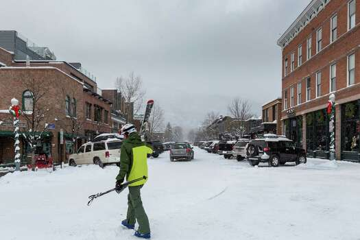 A skier strolls in central Aspen, where high-end boutiques thrive. Photo: Michael Paulsen, Staff / © 2012 Houston Chronicle