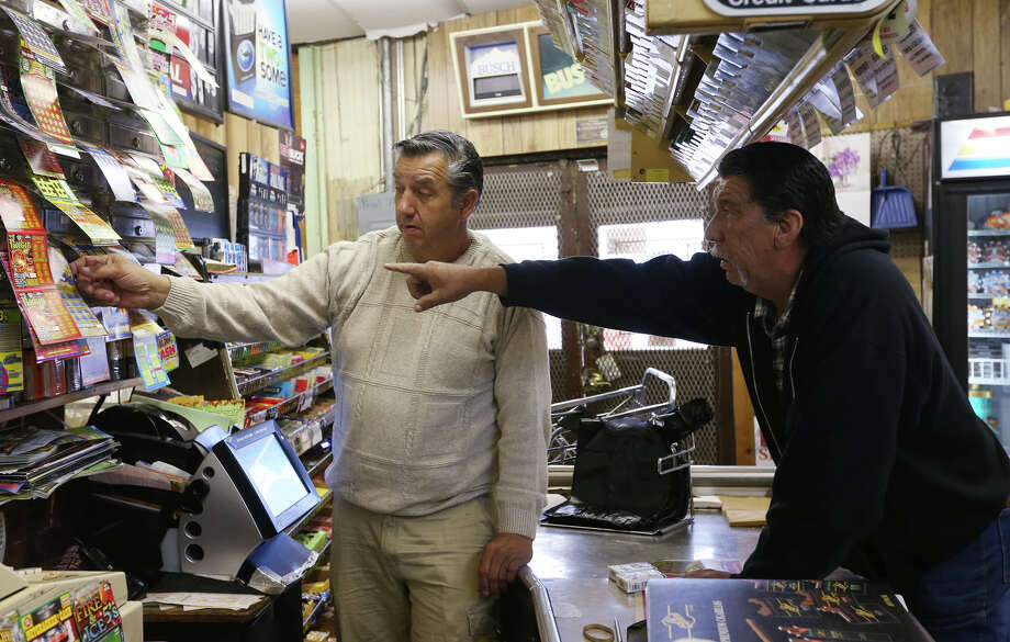 Larry Magott of Magott's Grocery & Market (left) attends to Reuben Rodriguez, who's busy selecting lottery tickets. Photo: Jerry Lara, San Antonio Express-News / © 2013 San Antonio Express-News
