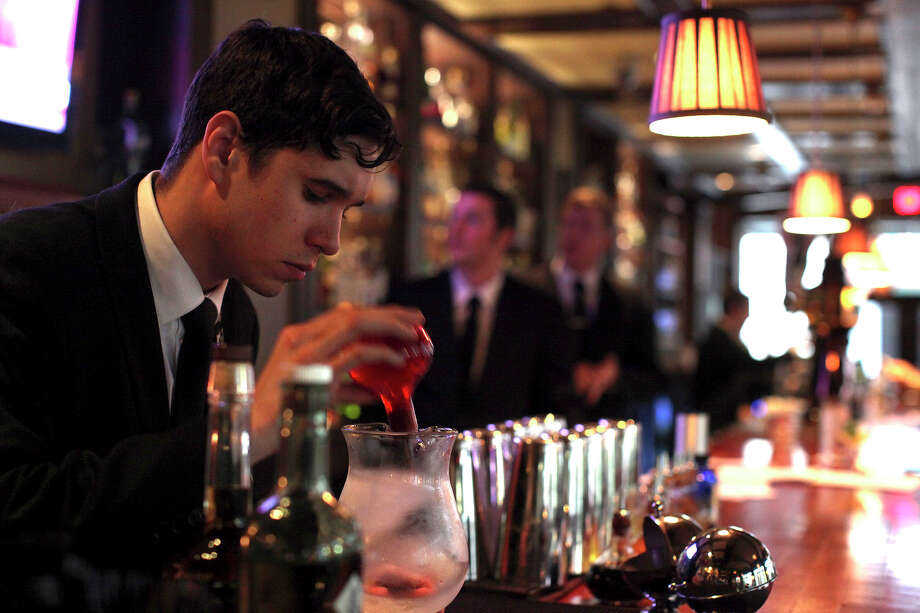 A glass of wine or a cocktail at a business lunch, while not verboten, is generally not done around here.   In this file photo, Head bartender Jake Corney makes Sazerac drinks at Bohanan's. Photo: Lisa Krantz, San Antonio Express-News / © 2012 San Antonio Express-News