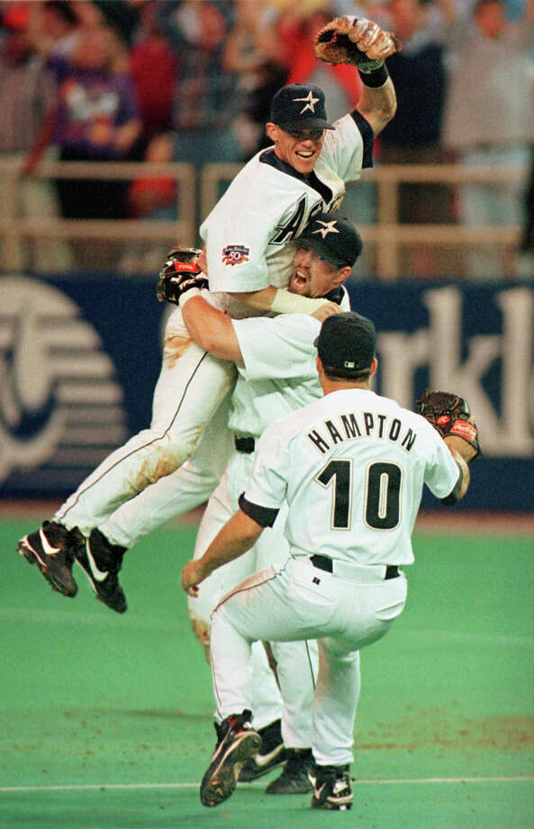 Jeff Bagwell hoists Craig Biggio as Mike Hampton joins the celebration after the Astros clinched the Central Division Championship on Sept. 25, 1997. It was the second time in Biggio's career that he led the Majors in runs scored.
