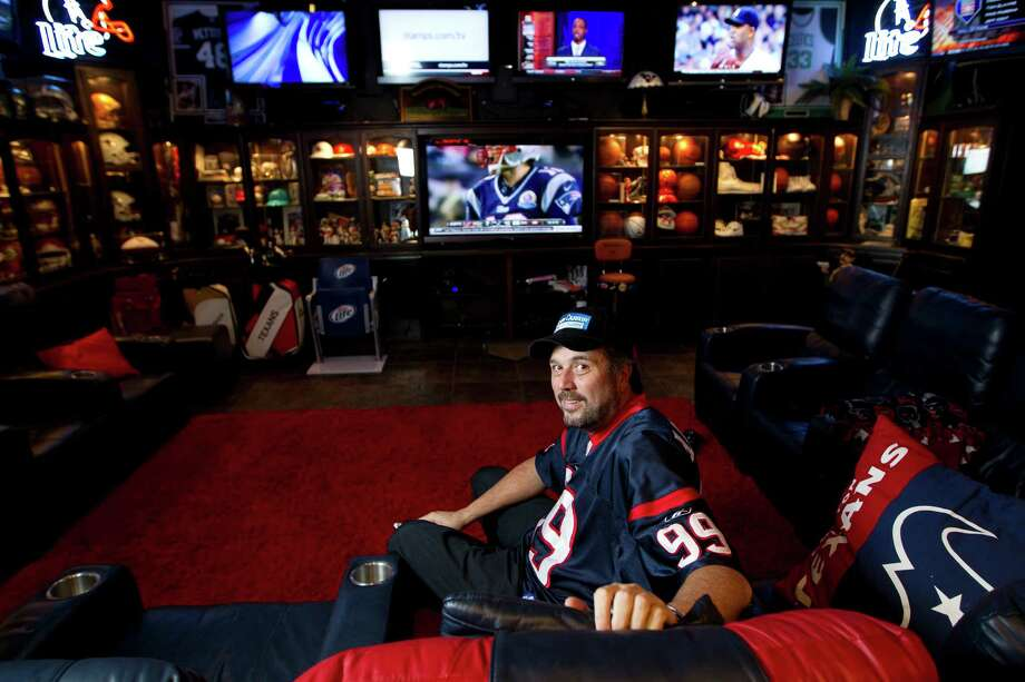 Blake Barnes, a Texans fan, stands in his man cave that can seat about 50 people with multiple televisions, and cabinets full of sports memorabilia and other collectibles, Wednesday, Jan. 9, 2013, in Deer Park.Read more about it here. Photo: Karen Warren, Houston Chronicle / © 2013 Houston Chronicle