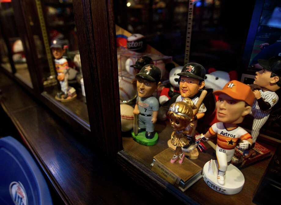 Detail of a cabinet full of bobble heads that reside in a man cave that Blake Barnes, a Texans fan,  created that can seat about 50 people with multiple televisions, and hundreds of sports memorabilia, Wednesday, Jan. 9, 2013, in Deer Park. Photo: Karen Warren, Houston Chronicle / © 2013 Houston Chronicle