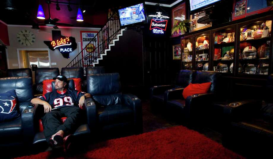 Blake Barnes, a Texans fan, stands in his man cave that can seat about 50 people with multiple televisions, and cabinets full of sports memorabilia and other collectibles, Wednesday, Jan. 9, 2013, in Deer Park. Photo: Karen Warren, Houston Chronicle / © 2013 Houston Chronicle