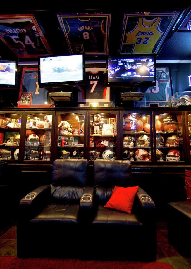 Sports memorabilia fills  a man cave that Blake Barnes, a Texans fan,  created that can seat about 50 people with multiple televisions, and hundreds of sports memorabilia, Wednesday, Jan. 9, 2013, in Deer Park. Photo: Karen Warren, Houston Chronicle / © 2013 Houston Chronicle