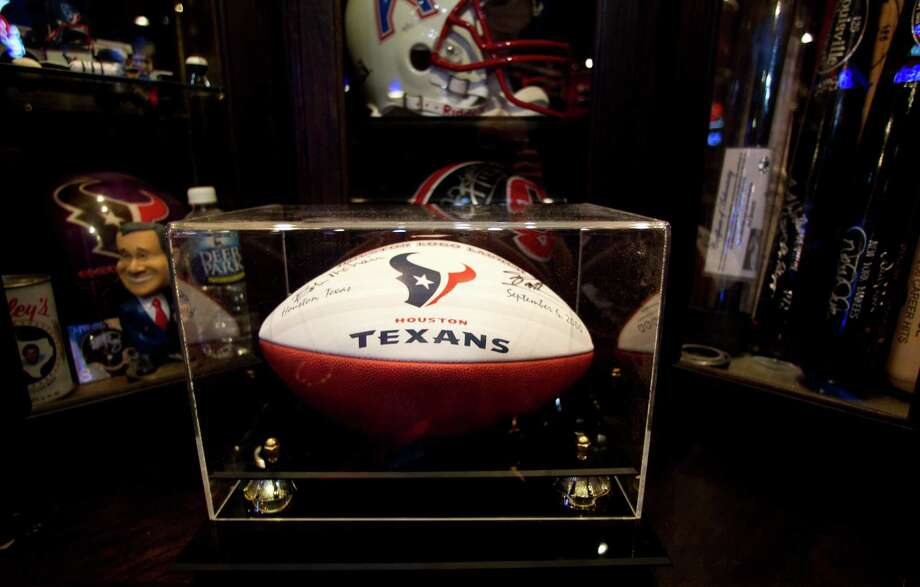 Detail of one of many signed footballs that reside in a man cave that Blake Barnes, a Texans fan,  created that can seat about 50 people with multiple televisions, and hundreds of sports memorabilia, Wednesday, Jan. 9, 2013, in Deer Park. Photo: Karen Warren, Houston Chronicle / © 2013 Houston Chronicle
