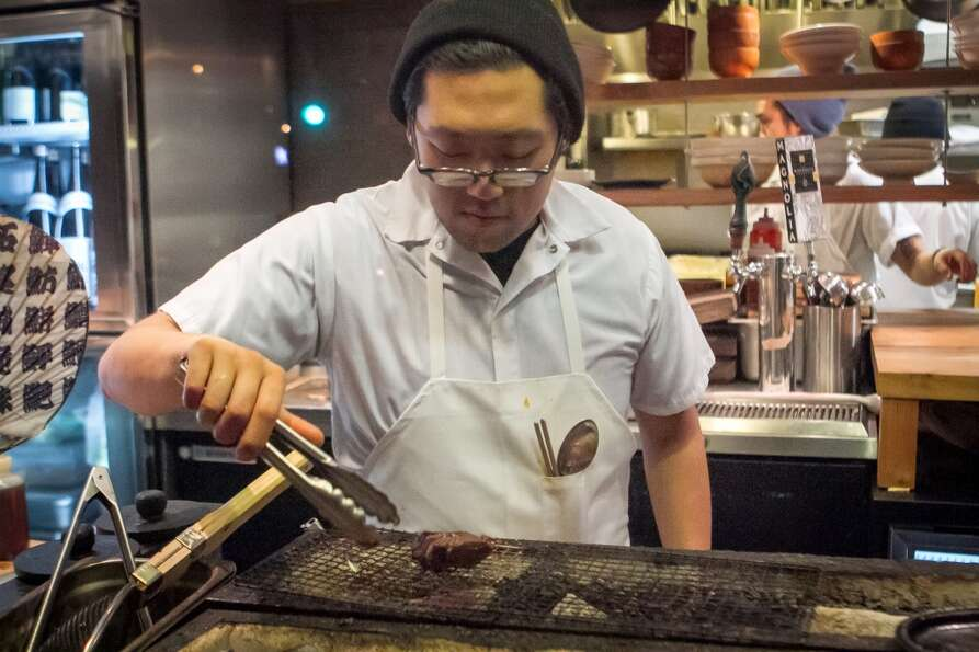 Sous chef Daniel Lim cooks a piece of beef.