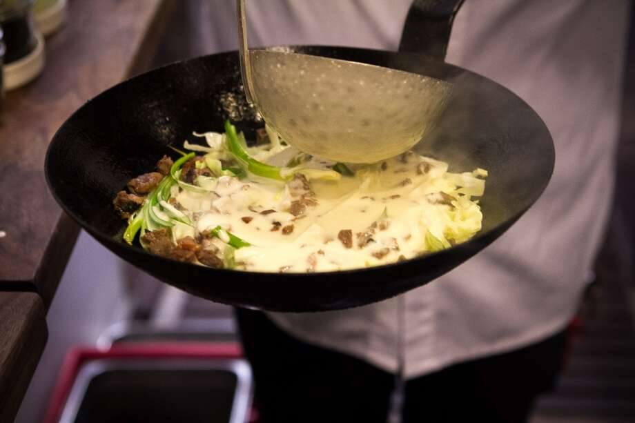 Sous chef Daniel Lim pours batter into a pan for okonomiyaki.