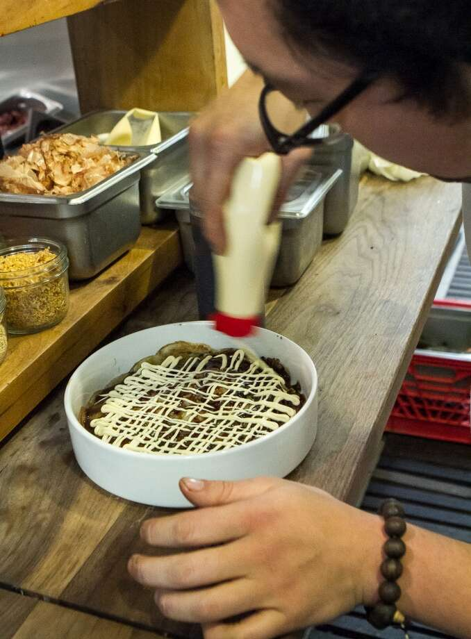 Sous chef Daniel Lim squeezes Japanese mayo onto the okonomiyaki.
