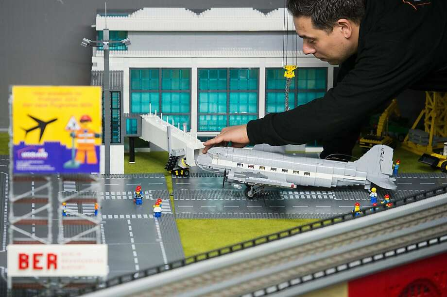 Vroom, vroom … Tower to Flight 1472, you're clear on runway 5 ... A Legoland employee plays with works on a Lego bricks model of Berlin's new main airport in Berlin. Photo: Maurizio Gambarini, AFP/Getty Images