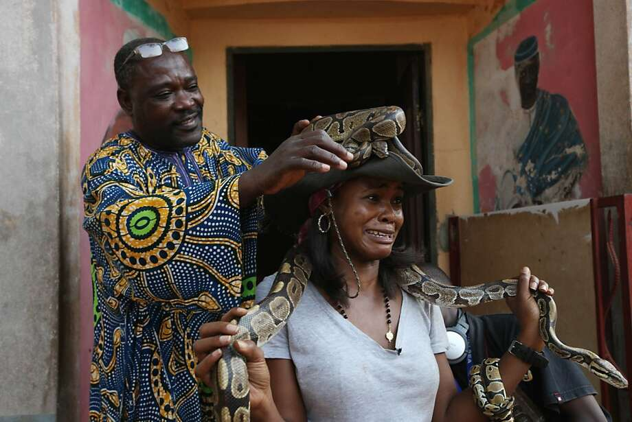If you visit the voodoo Temple of Pythons in Ouidah, Benin, be prepared to have a live python draped over your head. She wasn't. Photo: Sunday Alamba, Associated Press