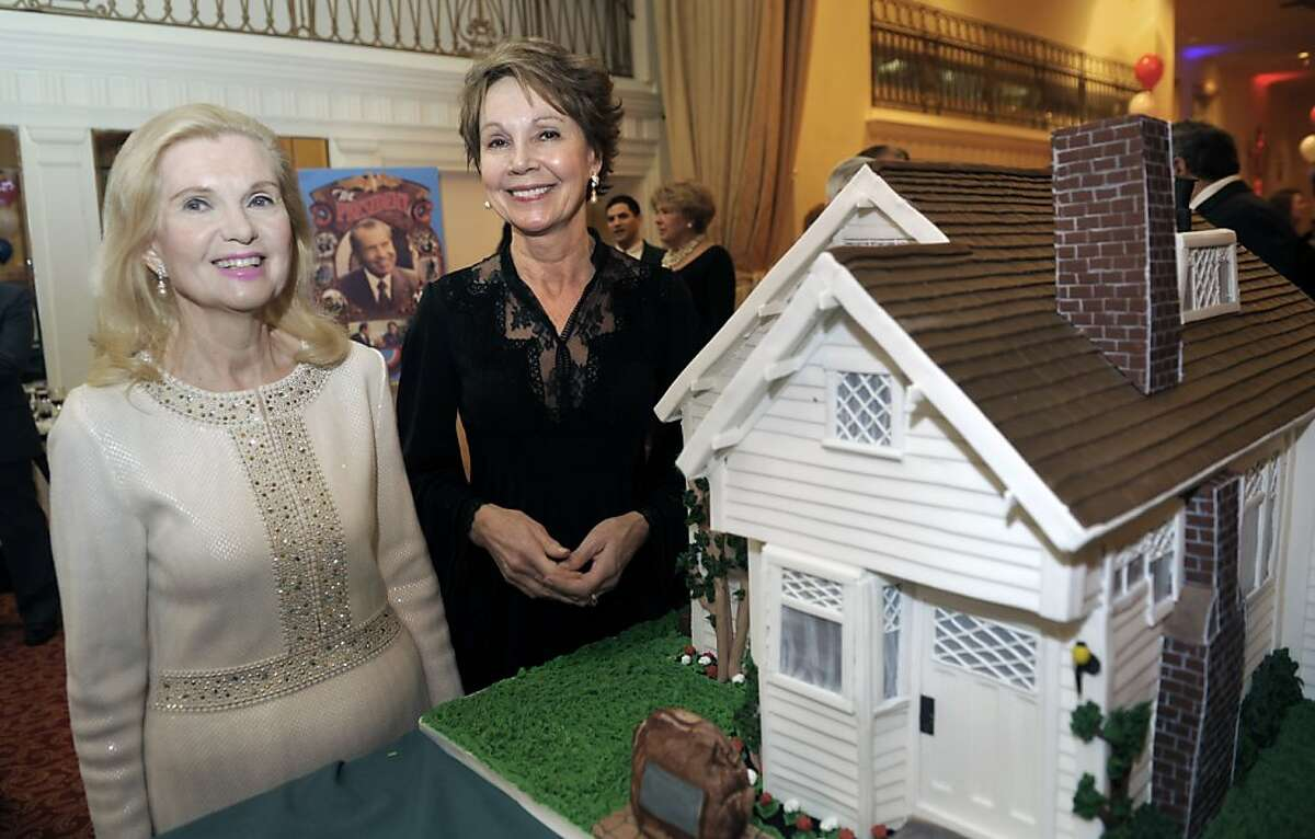 Trisha Nixon Cox, left, and Julie Nixon Eisenhower pose with a cake designed like their father, President Richard Nixon's, birthplace during the Richard Nixon Centennial Birthday Celebration in Washington, Wednesday, Jan. 9, 2013. The house, built by Nixon's father, Francis A. Nixon, from a home building kit.