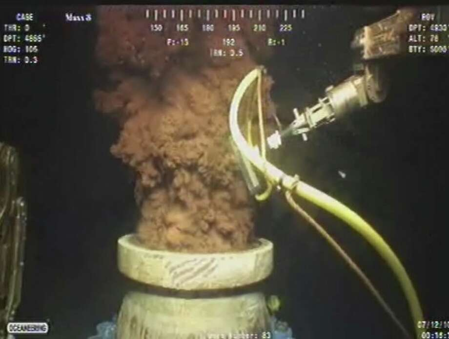 FILE   In this Monday July 12, 2010 image from video made available by BP PLC, oil flows out of the top of the transition spool, which was placed into the gushing wellhead and will house the new containment cap, at the site of the Deepwater Horizon oil spill in the Gulf of Mexico. An April 20, 2010 explosion at the offshore platform killed 11 men, and the subsequent leak released an estimated 172 million gallons of petroleum into the gulf. (AP Photo/BP PLC) Photo: (AP Photo/BP PLC), HONS