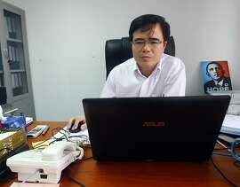 FILE - In this Friday, Sept. 28, 2012 file photo, Le Quoc Quan, a well-known dissident lawyer, works at his office in Hanoi, Vietnam. Vietnamese police have detained Quan, escalating a crackdown on those who speak out against the country's one-party, authoritarian rule. Quan was arrested on his way to drop off his children at school Thursday, Dec. 27, 2012 in Hanoi, according to the Vietnamese Redemptorist Church's website. The state-run Tuoi Tre newspaper reported Friday that Quan was detained for alleged tax evasion. (AP Photo/Na Son Nguyen, File)