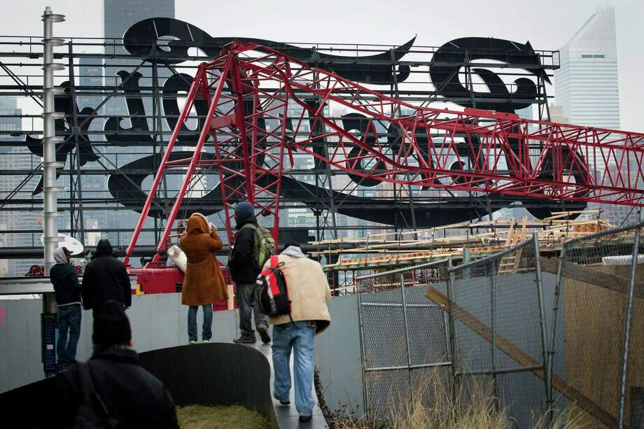 "Onlookers observe a mangled crane at the construction site in the Queens borough of New York where it collapsed, Wednesday, Jan. 9, 2013 behind a big neon ""Pepsi Cola"" sign, a local landmark. The Fire Department of New York says the 200-foot crane collapsed onto a building under construction, injuring seven people, three of them seriously. (AP Photo/John Minchillo) Photo: John Minchillo"