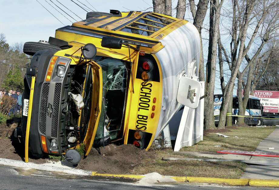 An overturned school bus rests on a fence after colliding with a commuter bus, back right, Thursday, Jan.10, 2013, in Old Bridge, N.J.   School officials said no students were on the Old Bridge school bus, which landed on its side along Route 9. (AP Photo/Mel Evans) Photo: Mel Evans