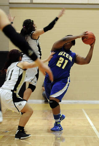 Lady Panther Nekia Jones, #21, tries to pass the ball with Lady Pirates all over her during the Vidor High School Lady Pirates basketball game against the Ozen High School Lady Panthers on Tuesday December 21, 2012, at Vidor High School. Ozen won over Vidor 64 - 58. Photo taken: Randy Edwards/The Enterprise Photo: Randy Edwards