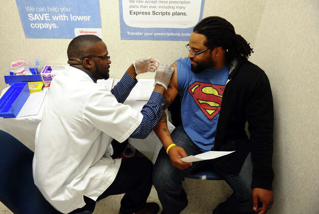 Yves Jean, of Bridgeport, right, receives a flu shot from pharmacist Dennis Johnson at a Walgreen's in Fairfield, Conn. on Thursday January 10, 2013. Photo: Christian Abraham / Connecticut Post