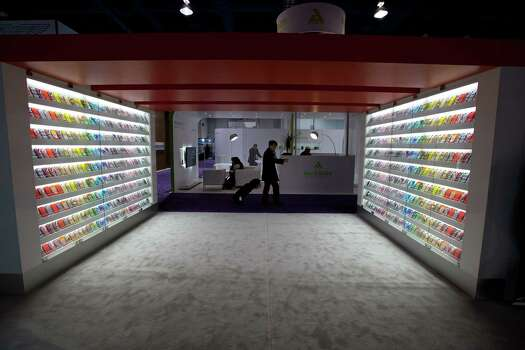 An attendee walks past shelves displaying smartphone covers at the 2013 Consumer Electronics Show in Las Vegas, Nevada, U.S., on Wednesday, Jan. 9, 2013. The 2013 CES trade show, which runs until Jan. 11, is the world's largest annual innovation event that offers an array of entrepreneur focused exhibits, events and conference sessions for technology entrepreneurs. Photographer: David Paul Morris/Bloomberg Photo: David Paul Morris, Bloomberg / © 2013 Bloomberg Finance LP