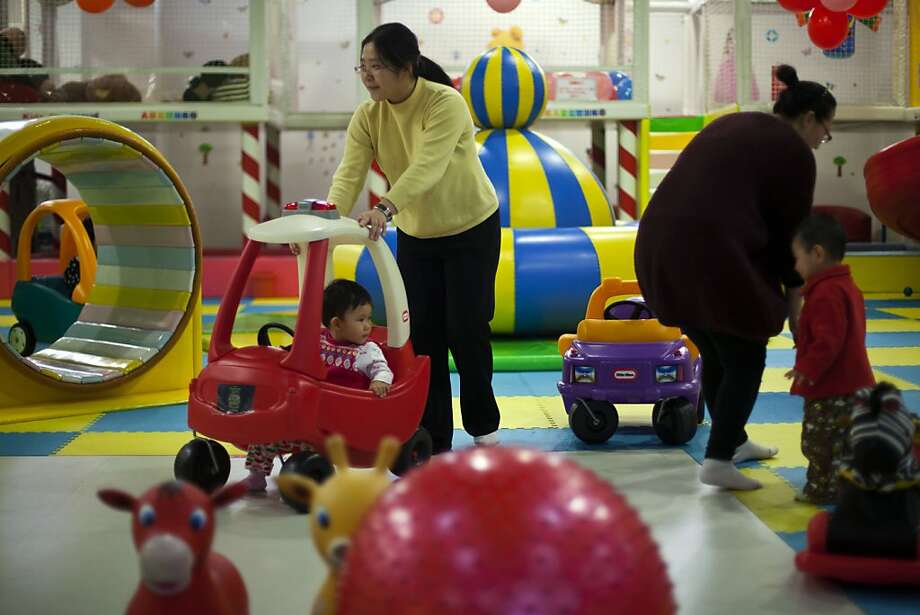 Parents play with their children at a kid's play area in a shopping mall in Beijing Thursday, Jan. 10, 2013. In China, a law that generally limits urban families to having just one child. They grow up as the sole focus of doting parents. How does this affect them? What does it mean to Chinese society if generations of kids are raised this way? Authors of a new study say the one-child policy has significant ramifications for Chinese society. Photo: Alexander F. Yuan, Associated Press