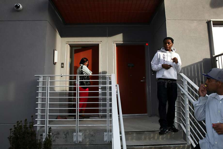 Angel Zinn, left, locks up her new apartment as her son, Marvin Carter, center, and boyfriend, Brist McConico, right, wait for her at the Hunters View housing complex in San Francisco, Calif., on Monday, January 7, 2013. The brand new Hunters View revitalization project has finished its first phase and people are moving into the housing that is designed for public housing, affordable rentals and first-time homebuyers where the former Bayview Hunters Point public housing once stood. Photo: Carlos Avila Gonzalez, The Chronicle