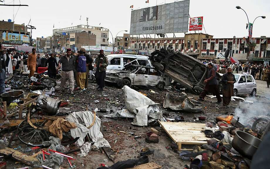 Pakistani police officers and local residents gather at the site of a bomb blast that targeted paramilitary soldiers in a commercial area in Quetta, Pakistan, killing at least 12 people and wounding more than 40 others, according to police, Thursday, Jan. 10, 2013. A series of bombings in different parts of Pakistan killed 115 people on Thursday in one of the deadliest days in the country in recent years. Photo: Arshad Butt, Associated Press