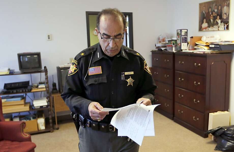 Jefferson County Sheriff Fred Abdalla  studies printouts of an anonymous Facebook post in which he and his family were threatened as he investigates reports that athletes raped a girl. Photo: Keith Srakocic, Associated Press