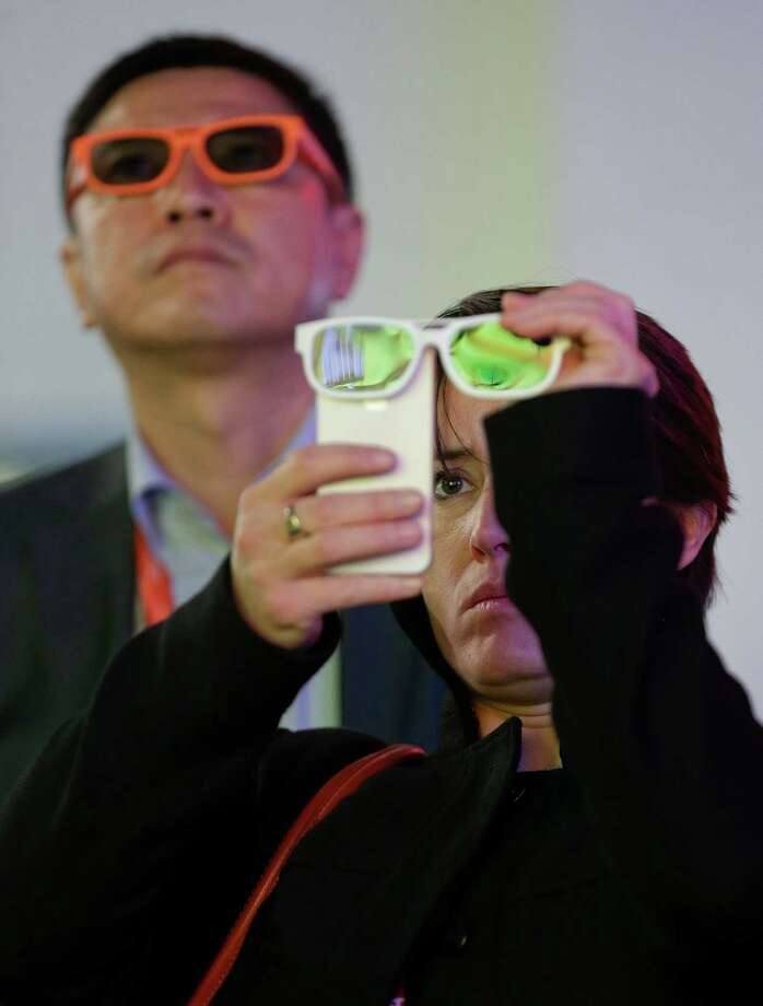 Buyer Julie Carpenter records 3-D video with her iPhone through a pair of 3-D glasses at the Consumer Electronics Show, Thursday, Jan. 10, 2013, in Las Vegas. (AP Photo/Julie Jacobson) Photo: Julie Jacobson