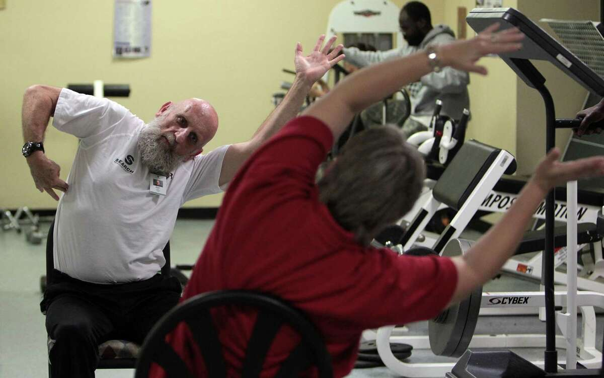Don Hall, left, gives chair yoga instructions to Teresa Terrill, right, during an exercise class he leads at SEARCH. Hall is a recovered former drug addict who is tackling the half-marathon Sunday.